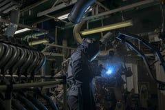 Industriearbeiter schweißen Automobil die Stahlteile Lizenzfreie Stockfotos
