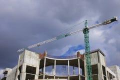 Industriebaukran auf Baustelle über drastischem Himmel Stockfotos