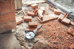 Industriebaustandortwerkzeuge, Winkelschleifer benutzt für den Schnitt von Ziegelsteinen an der Gebäudeerneuerung, Rekonstruktion Stockbild
