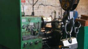 Industrieel Concept Bouwinstallatie Een slot die op de haak hangen Een mens die met een draaibank aan de achtergrond werken stock videobeelden
