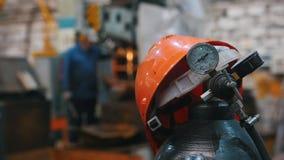 Industrieel concept - rode helm op de gasfles voor lassen - installatie stock footage