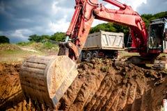 Industrieel graafwerktuig die een gat graven en aarde laden Stock Fotografie