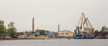 Industrieel landschap met haven en ladingskranen op rivier, het verschepen, handel en internationale logistisch stock afbeeldingen