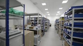 Industrieel Pakhuis Witmetaalrekken met blauwe plastic die dienbladen en kartondozen in hen worden geïnstalleerd stock video