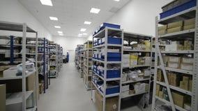 Industrieel Pakhuis Witmetaalrekken met blauwe plastic die dienbladen en kartondozen in hen worden geïnstalleerd stock footage