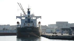Industrieel schip dat bij pijler met bulldozers het werken wordt gedokt stock footage