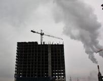 Industriegebäude des hohen Fabrikschornsteins mit Rauche lizenzfreies stockbild