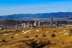 Industriegebiet herein im Hintergrund mit rauchenden Fabrikkaminen, -wald und -bergen Stockfotos