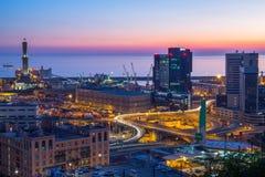 Industriegebiet nahe dem Hafen mit Lanterna und Handelswolkenkratzern bei Sonnenuntergang, Genua, Italien lizenzfreie stockfotos
