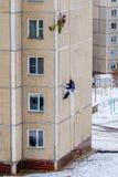 Industriekletterer reparieren die Gelenke zwischen den Platten eines Wohngebäudes Stockfoto