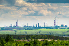 Industrielandschaft mit einer Erdölraffinerie auf dem grünen Hügel Stockfotografie