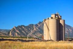 Industriell åkerbruk hisssilo med berg Arkivfoto