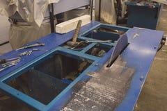 Industriell automatisk utrustning för maskinhjälpmedel med det runda bladet, fabriks- träverkbakgrund för bransch arkivfoton