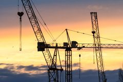 Industriell bakgrund med konturn av konstruktionskranen p? solnedg?ngen fotografering för bildbyråer