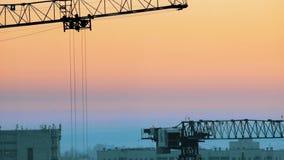 industriell Eine Baustelle mitten in der Stadt Hochziehen des Kranarbeitens Rosiger Sonnenuntergang stock footage
