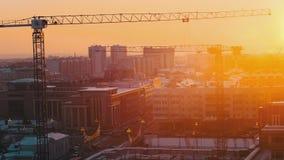 industriell Eine Baustelle mitten in der Stadt Hochziehen des Kranarbeitens Sonnenuntergang stock video footage