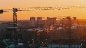 industriell Eine Baustelle mitten in der Stadt Hochziehen des Kranarbeitens Sonnenuntergang Statischer Schuss stock footage