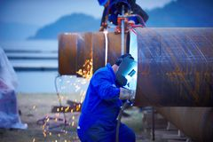 Industriell elektrodwelder med framsidaskölden och total- svetsning för blått ett stålrör i seminarium Arkivbilder