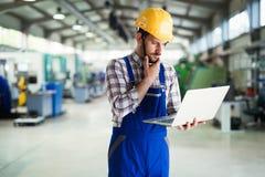Industriell fabriksanställd som arbetar i fabriks- bransch för metall arkivfoto