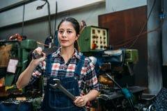 Industriell fabrikskvinna som rymmer stora skiftnycklar Arkivbild