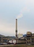 Industriell fabriksområdessikt med lampglasrök på förorening för blå himmel Arkivfoto