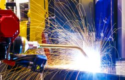 Industriell gul svetsning för uppförande för robotweldernärbilden av metalldelar, metallsmå droppar strilas beautifully in royaltyfri fotografi