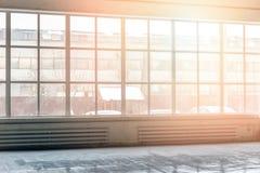 Industriell inre med det breda golvet till takfönstret Fabrik som bygger den genomskinliga väggen Solljus till och med fönster royaltyfria bilder