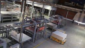Industriell inre, produktion av keramiska tegelplattor, modern fabriksinre, elektrisk automatiserad vägledd medelplattform arkivfilmer