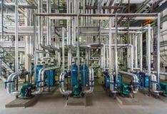 Industriell kokkärlinre med massor av rör, pumpar och ventiler arkivfoto