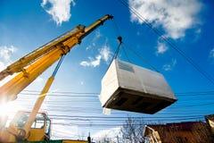 Industriell kran som fungerar och lyfter en elektrisk generator Arkivfoto