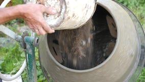 Industriell maskin för cementblandare på konstruktionsplatsen Tillfoga grus under blandning konkret hälla Blandar sanden, grus arkivfilmer