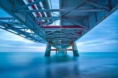 Industriell pir på havet. Nedersta sikt. Långt exponeringsfotografi. Arkivfoton
