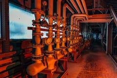 Industriell rörledning för stål med ventiler och manometrar i korridor av den övergav fabriken fotografering för bildbyråer
