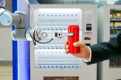 Industriell robotic gripa röd sodavatten kan för överföring till affärsmannen royaltyfria bilder