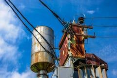 Industriell sikt av den rostiga transformatorasken, elektriska trådar och vattentornet med en stege på sidan Arkivbild