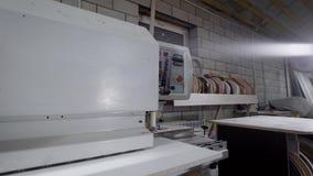 Industriell snickare som arbetar på kantrevärmaskinen på fabriken arkivfilmer