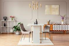 Industriell stil, guld- hängeljus ovanför en ovanlig marmortabell i en moderiktig matsalinre arkivfoton