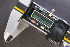 Industriell stilleben för Digital mikrometer på en svart bakgrund Fotografering för Bildbyråer
