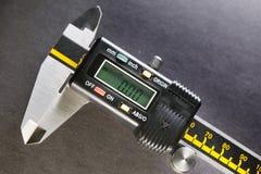 Industriell stilleben för Digital mikrometer på en svart bakgrund Royaltyfria Bilder