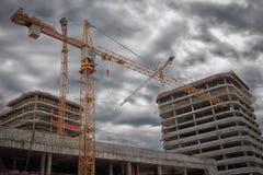 Industriell teknik Konstruktionskran på konstruktionsplatsen mot bakgrunden av nya fastighetbyggnader Royaltyfri Bild