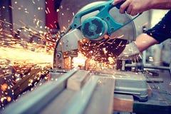 Industriell tekniker som arbetar på att klippa en metall och ett stål Arkivfoto
