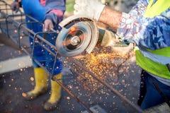 Industriell tekniker som arbetar på att klippa en metall- och stålstång med vinkelmolar Arkivbild