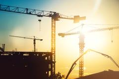 Industriell tung konstruktionsplats med tornkranar och byggnadskonturer arkivbilder