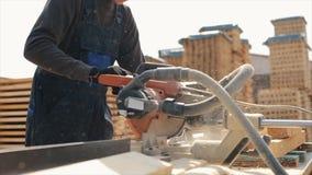 Industriell ung snickarearbetarwearuniforn som kommer till maskinen för nolla-träklipp mannen klipper träplankor lager videofilmer