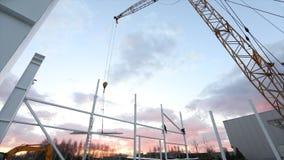 Industriell yttersida, montering av metallstrukturer mot bakgrunden av en orange himmel med moln, byggnation stock video