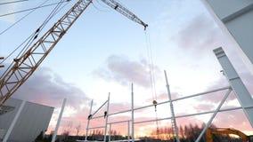 Industriell yttersida, montering av metallstrukturer mot bakgrunden av en orange himmel med moln, byggnation arkivfilmer