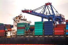 Industriella behållarelastfrakter sänder med den arbetande kranbron i skeppsvarv Arkivfoton