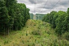 Industriella elströmlinjer gående berg 0ver Arkivbild