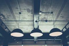 Industriella hängelampor mot den grova väggen, vindstil Arkivfoto