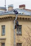 Industriella klättrare reparerar en stuprör på väggen av en bostads- byggnad royaltyfri bild